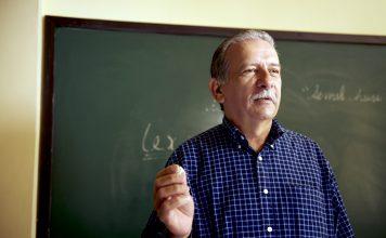 Professor in Havana, Cuba teaching in front of a blackboard.