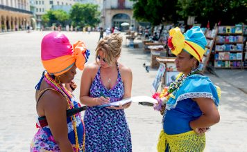Student interviewing two Cuban woman in traditional Cuban dresses.