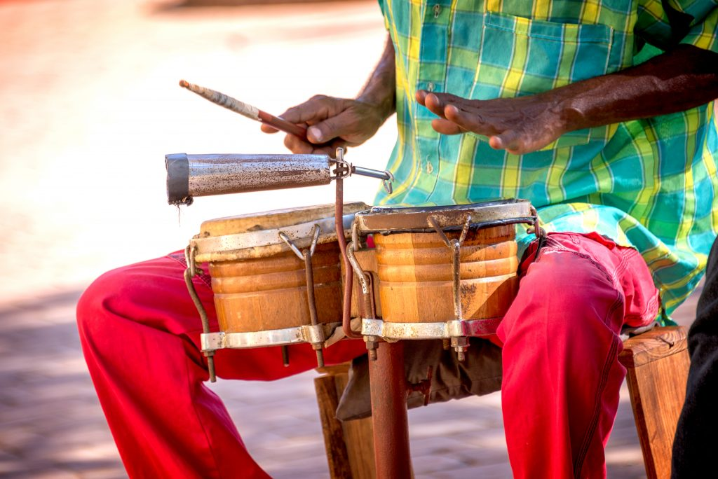 Cuban man playing small drums wearing brightly colored clothes.