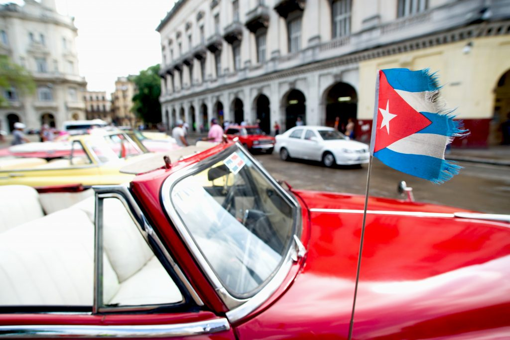 Antique car with Cuban flag on antenna.