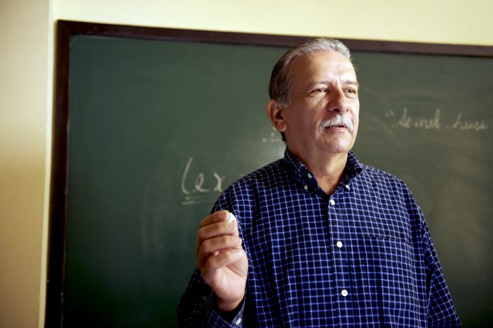 Professor in Havana, Cuba teaching in front of a blackboard.