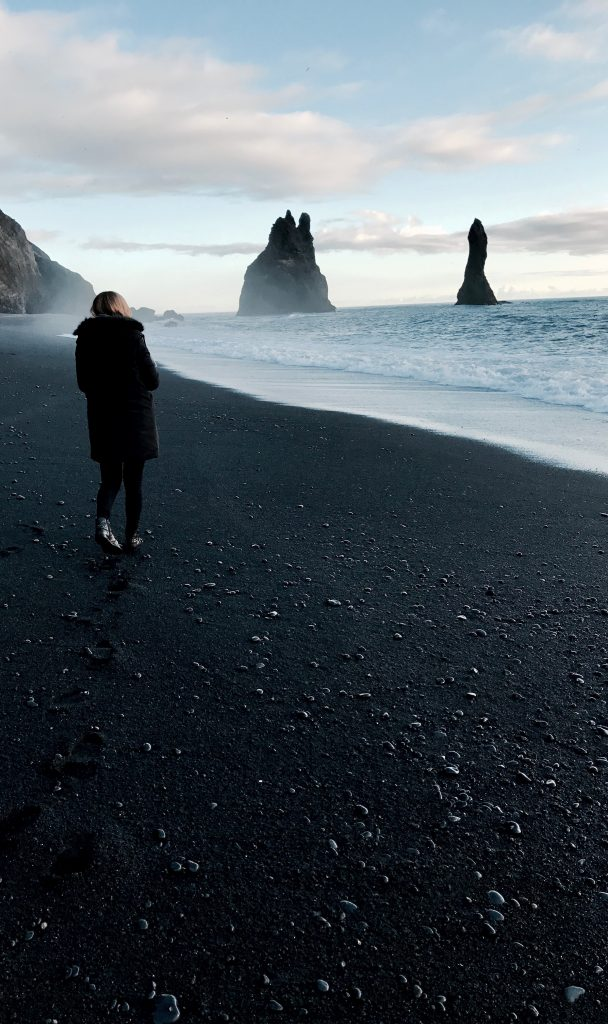 Student walking along the black sands of Hvitserkur Beach.
