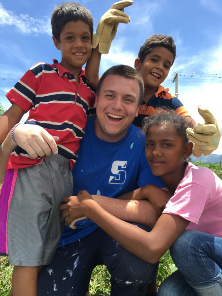 A student volunteer playing with kids on a service trip in the Dominican Republic.