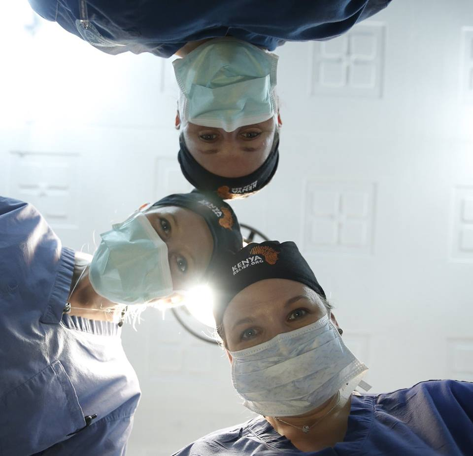 Three surgeons huddles around the operating table.