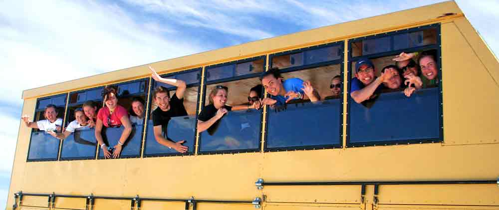 Group of students waving from a vehicle during a faculty-led trip to Africa.
