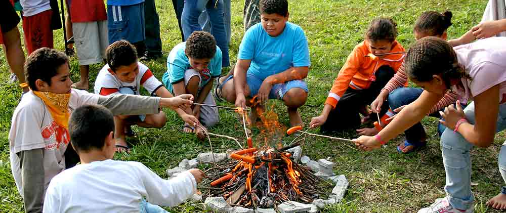 An American mission team shows local children how to cook hot dogs in a camp fire