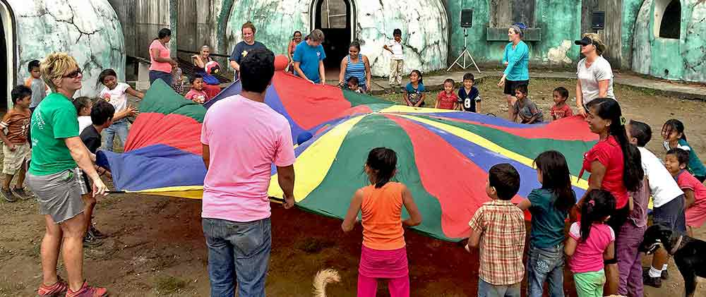 Group of kids and misson team members playing with a parachute