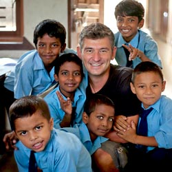 Professor takes a photo op with a group of children at a local school in India while on a short-term study abroad program focused on education.