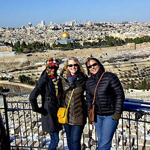 A group of travelers standing on the Mount of Olives in front of a panoramic view of Jerusalem, Israel.