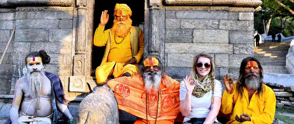 University student sitting with colorfully decorated sadhu men in Kathmandu, Nepal during a group study tour