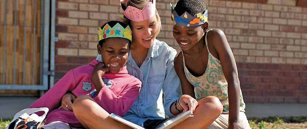 Volunteer reading a book to kids in South Africa